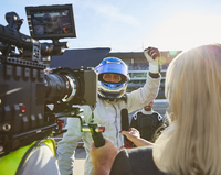 News reporter and cameraman interviewing formula one driver cheering, celebrating victory 11086033548| 写真素材・ストックフォト・画像・イラスト素材|アマナイメージズ