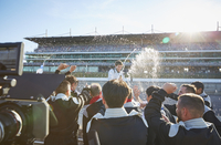 Formula one racing team spraying champagne on driver, celebrating victory on sports track 11086033550| 写真素材・ストックフォト・画像・イラスト素材|アマナイメージズ