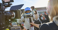 News reporter and cameraman interviewing formula one driver cheering, celebrating victory 11086033551| 写真素材・ストックフォト・画像・イラスト素材|アマナイメージズ