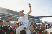 Formula one racing team carrying cheering driver on shoulders, celebrating victory on sports track 11086033593| 写真素材・ストックフォト・画像・イラスト素材|アマナイメージズ
