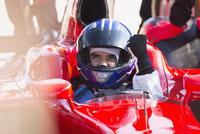 Formula one race car driver in helmet gesturing, celebrating victory 11086033605| 写真素材・ストックフォト・画像・イラスト素材|アマナイメージズ