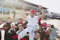 Formula one racing team carrying driver on shoulders, celebrating victory on sports track 11086033608| 写真素材・ストックフォト・画像・イラスト素材|アマナイメージズ