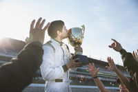 Formula one racing team cheering around driver kissing trophy, celebrating victory 11086033610| 写真素材・ストックフォト・画像・イラスト素材|アマナイメージズ