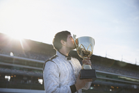 Male formula one driver kissing trophy, celebrating victory on sports track 11086033635| 写真素材・ストックフォト・画像・イラスト素材|アマナイメージズ