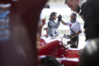 Manager and formula one race car driver high-fiving in repair garage 11086033652| 写真素材・ストックフォト・画像・イラスト素材|アマナイメージズ