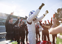 Formula one racing team and driver cheering, celebrating victory on sports track 11086033654| 写真素材・ストックフォト・画像・イラスト素材|アマナイメージズ