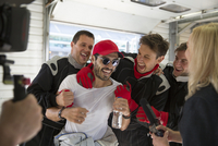 Formula one driver and team celebrating victory in repair garage 11086033660| 写真素材・ストックフォト・画像・イラスト素材|アマナイメージズ