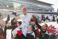 Formula one racing team carrying driver with trophy on shoulders, celebrating victory on sports track 11086033664| 写真素材・ストックフォト・画像・イラスト素材|アマナイメージズ