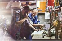 Motorcycle mechanics working in workshop 11086033681| 写真素材・ストックフォト・画像・イラスト素材|アマナイメージズ