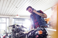 Motorcycle mechanic talking on cell phone in workshop 11086033691| 写真素材・ストックフォト・画像・イラスト素材|アマナイメージズ