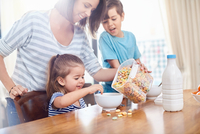 Mother pouring cereal for daughter at breakfast table 11086033728| 写真素材・ストックフォト・画像・イラスト素材|アマナイメージズ