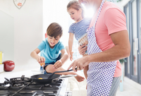 Father cooking breakfast at stove with daughter and son 11086033738| 写真素材・ストックフォト・画像・イラスト素材|アマナイメージズ