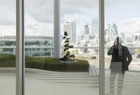 Businessman talking on cell phone on balcony with urban city view, London, UK 11086033900| 写真素材・ストックフォト・画像・イラスト素材|アマナイメージズ