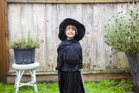 Portrait enthusiastic girl wearing witch costume in garden 11086034030| 写真素材・ストックフォト・画像・イラスト素材|アマナイメージズ