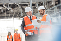 Male engineers with blueprints and clipboard discussing paperwork at construction site 11086034124| 写真素材・ストックフォト・画像・イラスト素材|アマナイメージズ