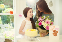 Affectionate daughter giving flower bouquet to mother on Mother's Day 11086034237| 写真素材・ストックフォト・画像・イラスト素材|アマナイメージズ