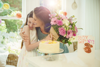 Affectionate daughter giving flower bouquet to mother on Mother's Day 11086034255| 写真素材・ストックフォト・画像・イラスト素材|アマナイメージズ