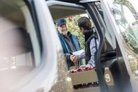 Male farmer and customer handshaking at truck in apple orchard 11086034303| 写真素材・ストックフォト・画像・イラスト素材|アマナイメージズ