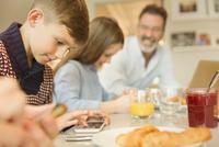 Boy using cell phone at breakfast table 11086034423| 写真素材・ストックフォト・画像・イラスト素材|アマナイメージズ