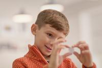 Curious boy holding coin 11086034528| 写真素材・ストックフォト・画像・イラスト素材|アマナイメージズ