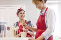 Smiling female caterers baking, making cupcake pops in kitchen 11086034549| 写真素材・ストックフォト・画像・イラスト素材|アマナイメージズ