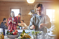 Woman tossing salad for friends in cabin 11086034584| 写真素材・ストックフォト・画像・イラスト素材|アマナイメージズ