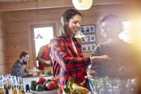Friends tossing salad in cabin 11086034586| 写真素材・ストックフォト・画像・イラスト素材|アマナイメージズ