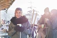 Portrait smiling female skier drinking coffee on cabin deck with friends apres-ski 11086034591| 写真素材・ストックフォト・画像・イラスト素材|アマナイメージズ