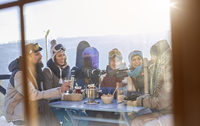 Snowboarder friends drinking and eating at balcony table apres-ski 11086034592| 写真素材・ストックフォト・画像・イラスト素材|アマナイメージズ