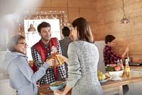 Friends toasting beer bottles in cabin kitchen 11086034613| 写真素材・ストックフォト・画像・イラスト素材|アマナイメージズ