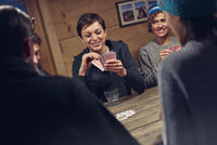 Friends playing cards at cabin table 11086034614| 写真素材・ストックフォト・画像・イラスト素材|アマナイメージズ
