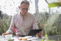 Senior man using digital tablet and drinking coffee at patio table 11086035218| 写真素材・ストックフォト・画像・イラスト素材|アマナイメージズ