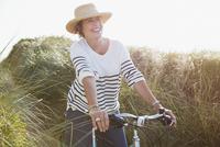 Smiling mature woman riding bicycle on sunny beach grass path 11086035220  写真素材・ストックフォト・画像・イラスト素材 アマナイメージズ