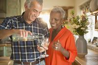 Smiling senior couple pouring white wine in kitchen 11086035226| 写真素材・ストックフォト・画像・イラスト素材|アマナイメージズ