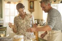 Playful mature couple baking in kitchen 11086035228| 写真素材・ストックフォト・画像・イラスト素材|アマナイメージズ