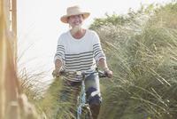Smiling mature woman riding bicycle along beach grass 11086035229  写真素材・ストックフォト・画像・イラスト素材 アマナイメージズ