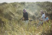 Mature couple walking bicycles in sunny beach grass 11086035232  写真素材・ストックフォト・画像・イラスト素材 アマナイメージズ