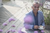 Portrait smiling senior man drinking coffee on sunny patio 11086035233| 写真素材・ストックフォト・画像・イラスト素材|アマナイメージズ