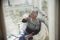 Senior man talking on cell phone on sun porch 11086035240| 写真素材・ストックフォト・画像・イラスト素材|アマナイメージズ