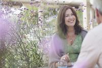 Smiling mature couple talking on patio with purple flowers 11086035263| 写真素材・ストックフォト・画像・イラスト素材|アマナイメージズ