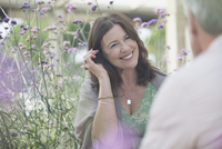 Smiling mature woman talking to man on patio with purple flowers 11086035299| 写真素材・ストックフォト・画像・イラスト素材|アマナイメージズ