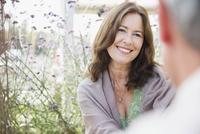 Mature woman smiling at man on patio 11086035311| 写真素材・ストックフォト・画像・イラスト素材|アマナイメージズ