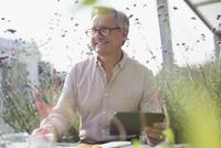 Smiling senior man using digital tablet on sunny patio 11086035313| 写真素材・ストックフォト・画像・イラスト素材|アマナイメージズ