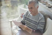 Senior man using digital tablet on sun porch 11086035334| 写真素材・ストックフォト・画像・イラスト素材|アマナイメージズ