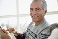Portrait smiling senior man using digital tablet 11086035337| 写真素材・ストックフォト・画像・イラスト素材|アマナイメージズ