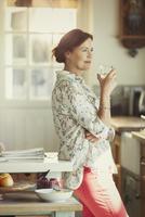 Pensive mature woman drinking wine in kitchen 11086035342| 写真素材・ストックフォト・画像・イラスト素材|アマナイメージズ