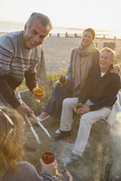 Smiling mature couples drinking wine and barbecuing on sunset beach 11086035349| 写真素材・ストックフォト・画像・イラスト素材|アマナイメージズ