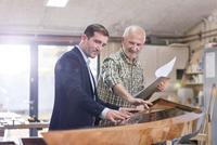 Male carpenter and customer examining wood kayak in workshop 11086035395| 写真素材・ストックフォト・画像・イラスト素材|アマナイメージズ