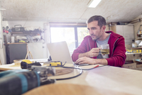 Male carpenter drinking tea and working at laptop on workbench in workshop 11086035399| 写真素材・ストックフォト・画像・イラスト素材|アマナイメージズ