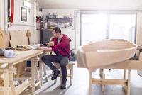 Male carpenter drinking tea and working at laptop on workbench in workshop 11086035400| 写真素材・ストックフォト・画像・イラスト素材|アマナイメージズ